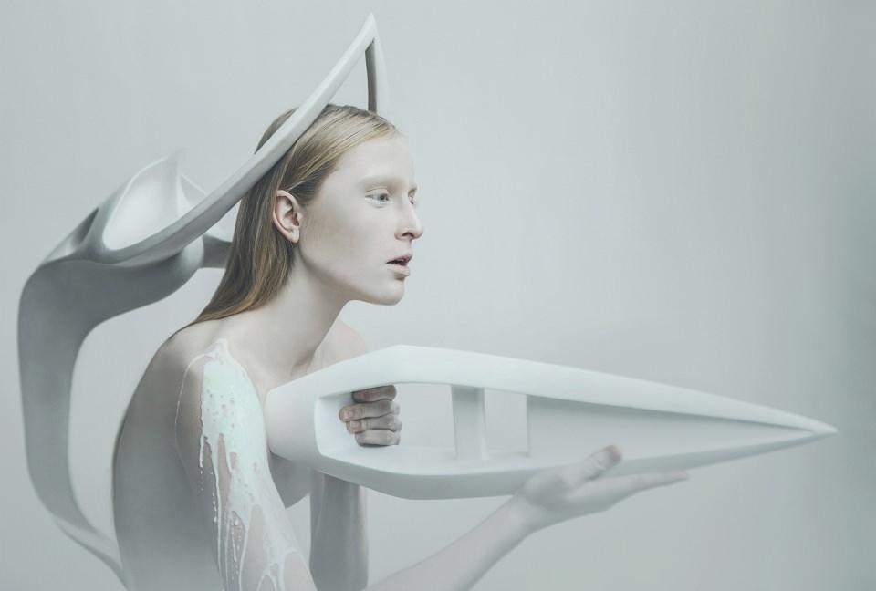 Portrait einer Frau mit zwei weißen Skulpturen und weißer Farbe.