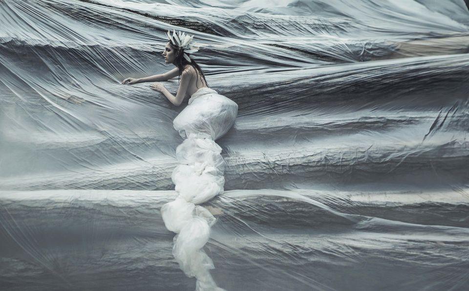 Portrait einer nackten, in Folie gehüllten Frau vor einer Wand aus Holzstämmen, ebenfalls in Folie verpackt.