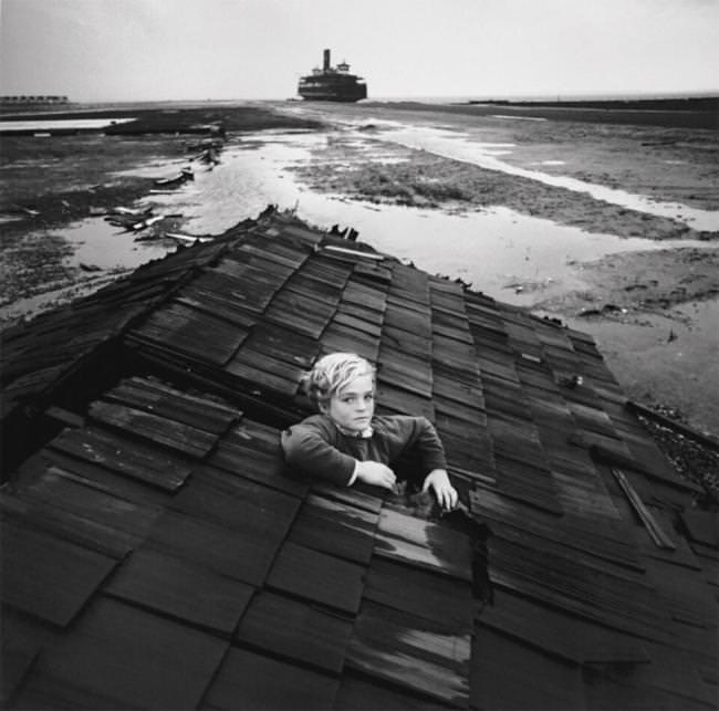 Ein Kind schaut aus dem Dach eines schwimmenden Hauses heraus.