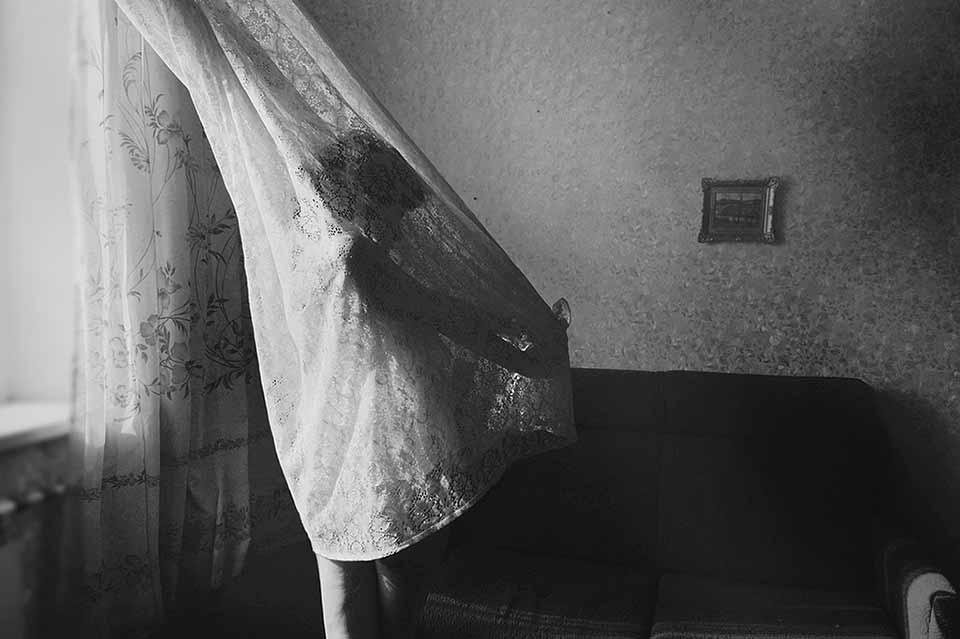 Eine Frau verheddert in Gardinen