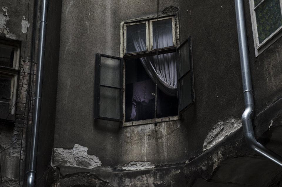 Häuserfassade, düster und mit einem geöffnetem Fenster