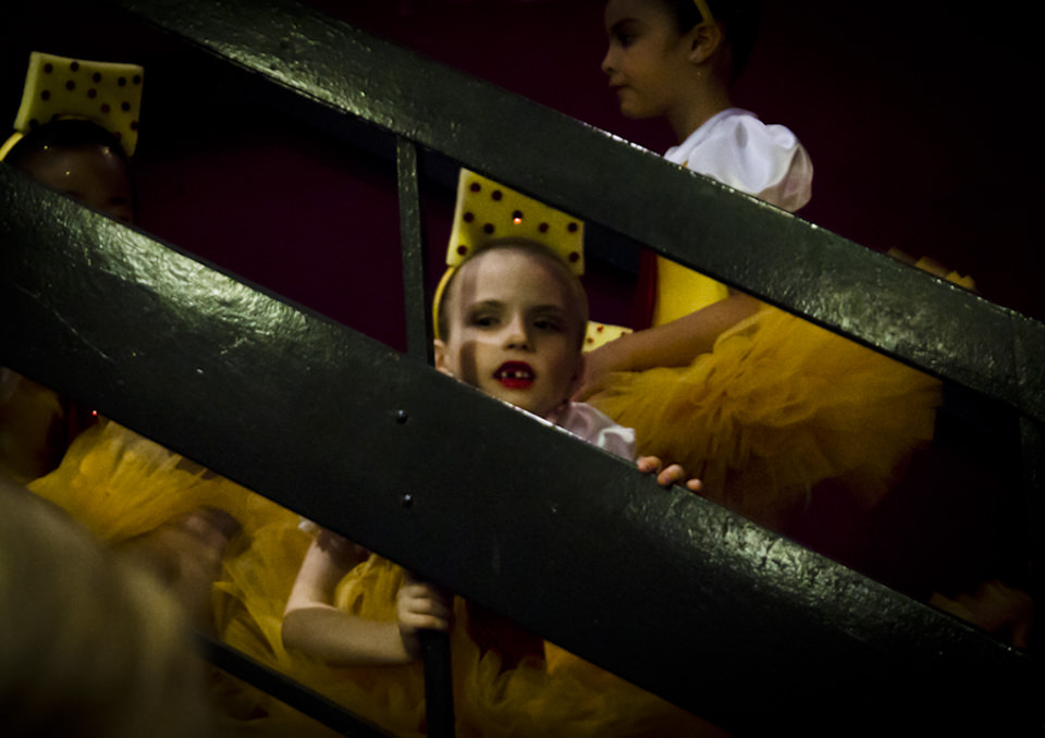 Ein Kind mit Zahnlücke lugt zwischen Brettern hindurch.