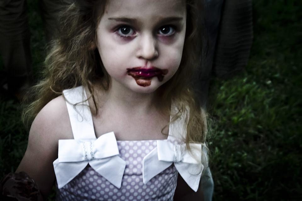 Ein schick angekleidetes Mädchen, das um den Mund herum verschmiert ist.