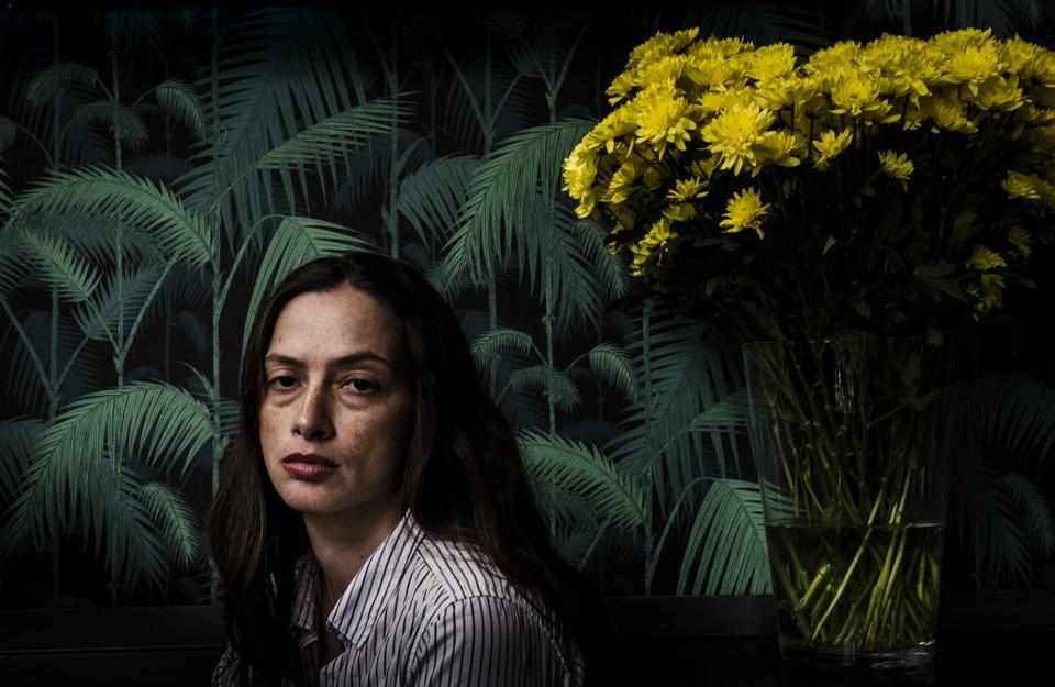 Eine Frau vor Blumen.
