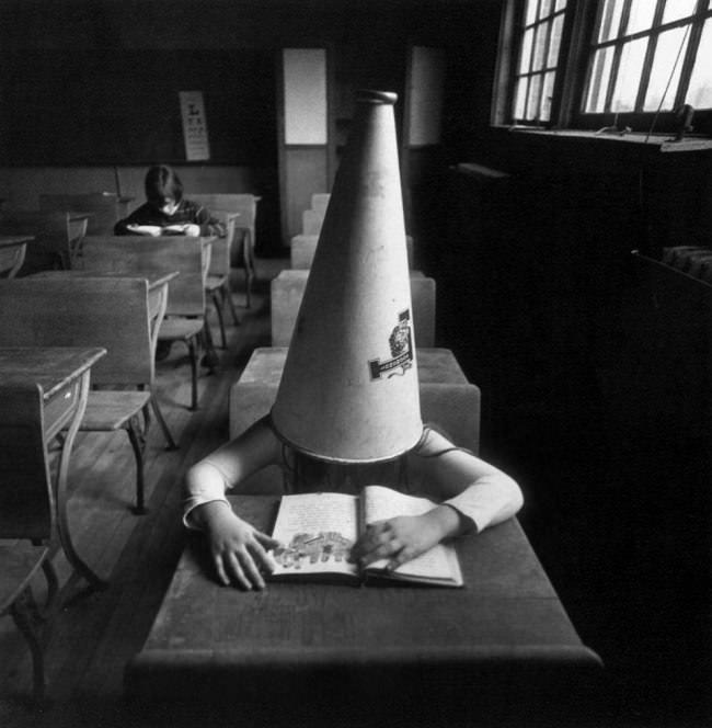 ein Mädchen trägt einen riesigen Kegel als Hut.