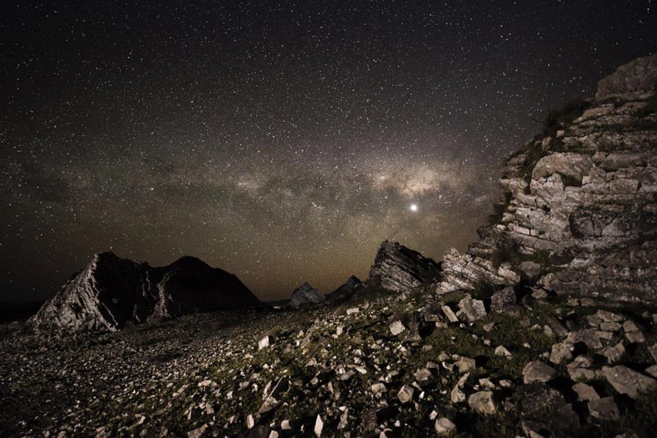 Über einer felsigen Landschaft ein Meer aus Sternen.