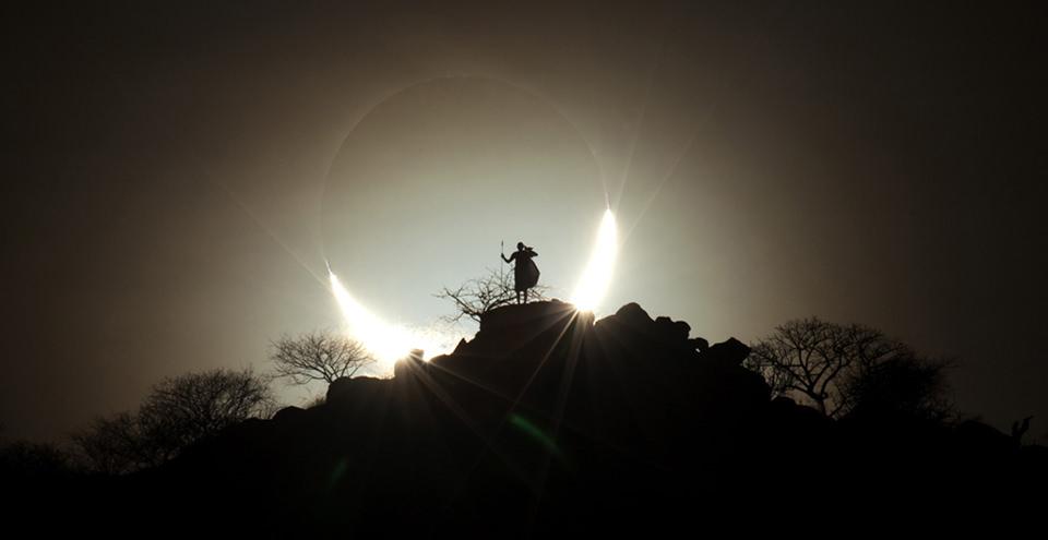 Ein Mensch auf einem Felsen, umringt von einer Sonnenfinsternis.