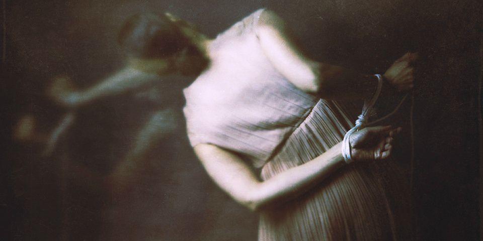 Frau mit hinterm Rücken verbundenen Armen.