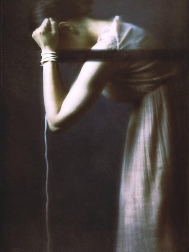 Frau im langem Kleid mit Fessel am Handgelenk.