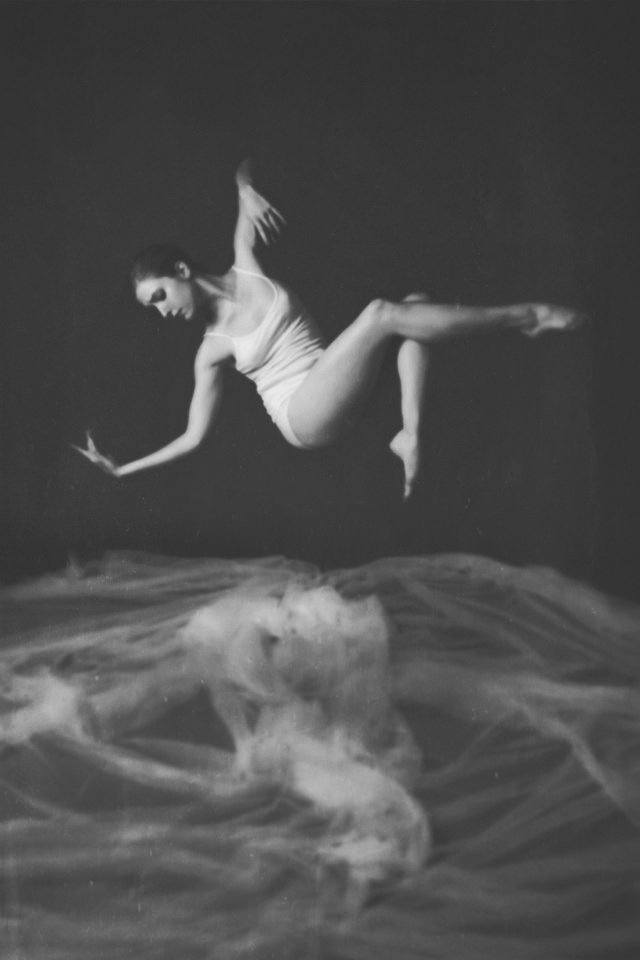 Frau in Unterwäsche schwebt in eleganter Pose über weißem Stoff am Boden.