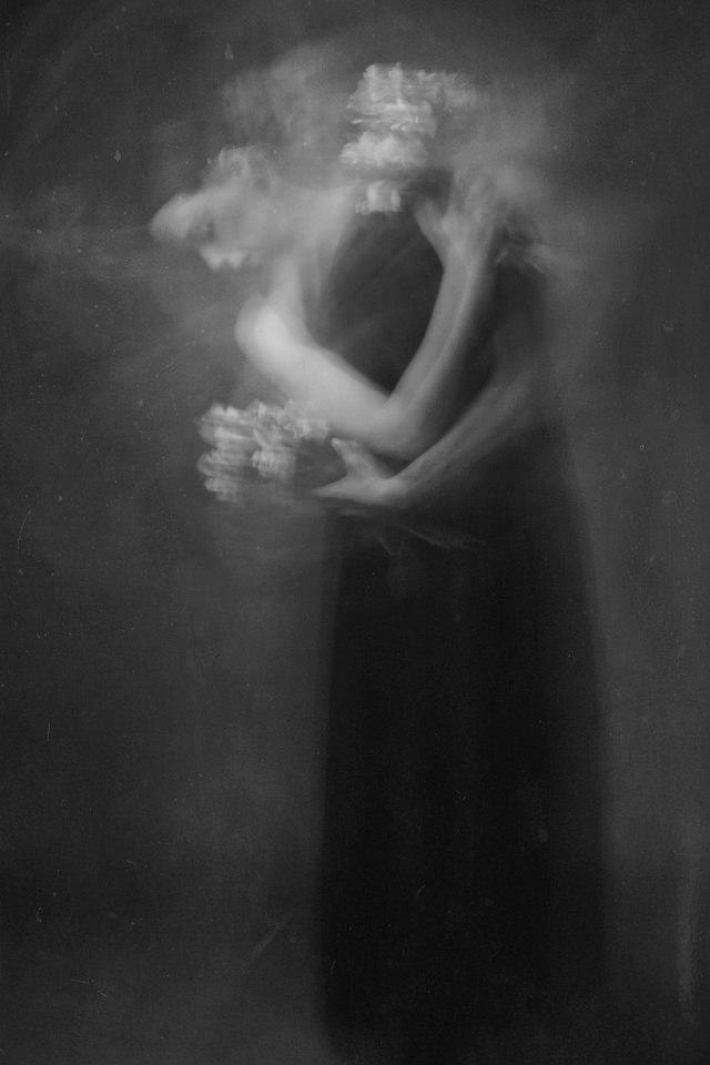 Frau in schwarzem Kleid mit Blumensträumen in den Händen.