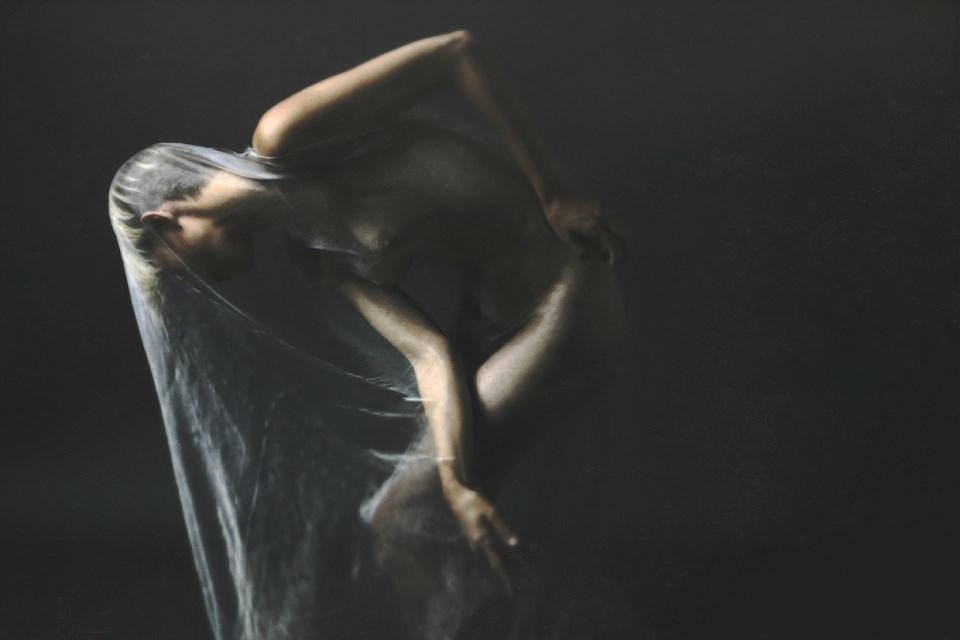 Akt mit transparentem Tuch in dunklem Licht.