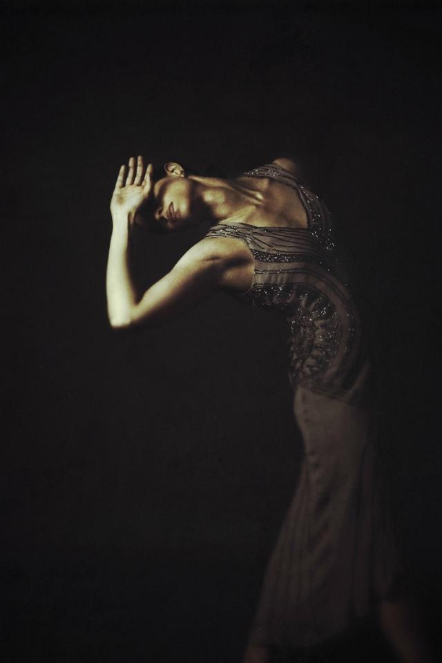 Frau in langem Kleid beugt sich nach hinten und hält eine Hand vors Gesicht.