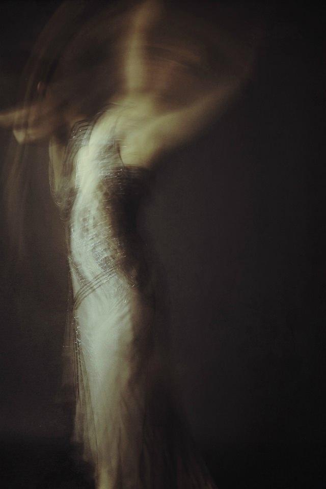 Unklares Bild einer Frau in langem Kleid, die sich nach oben reckt und nach vorn beugt.