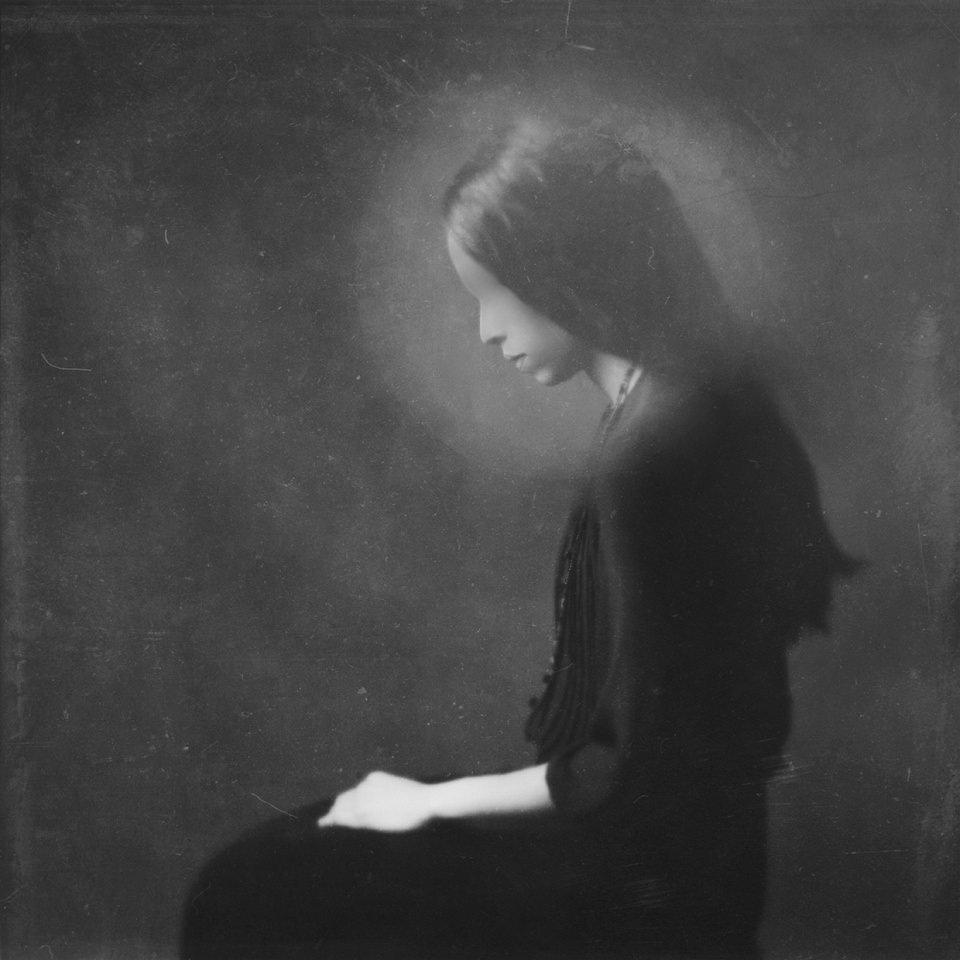 Seitliches Portrait einer sitzenden Frau mit Gesicht ohne Augen und Mund.