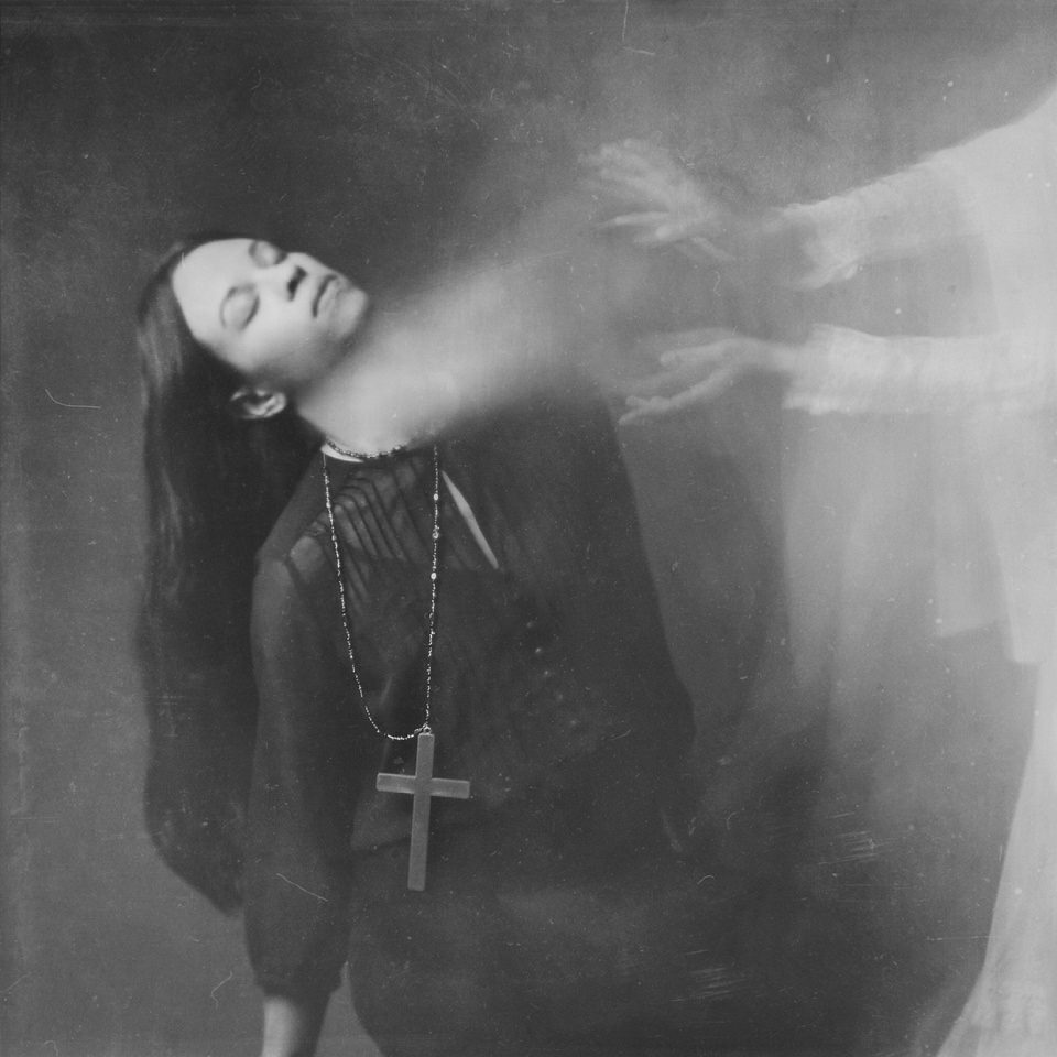 Frau mit einem großen Kreuz um den Hals, der Licht aus dem Hals zu leuchten scheint, das zwei Hände auffangen.