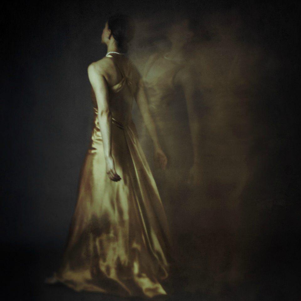 Frau in goldenem Kleid, umgeben von unklaren Mehrfachbelichtungen ihrer selbst.