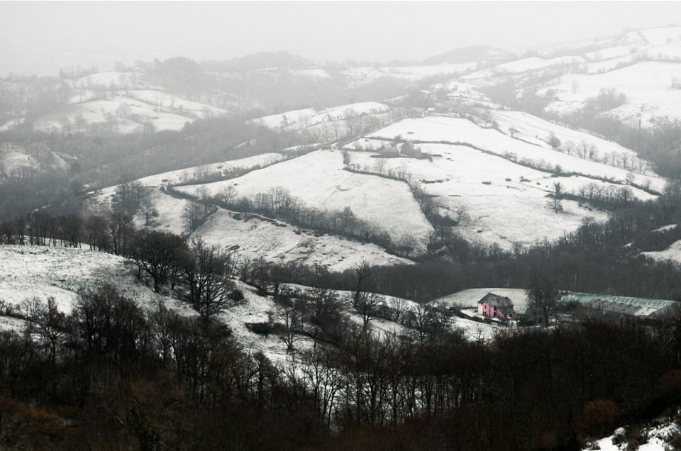 Blick über verschneite Felder in einem Tal.