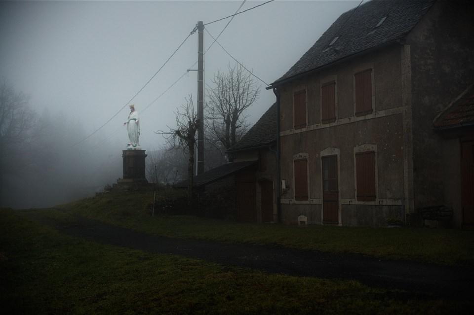 Hausecke mit Madonnenstatue im Nebel.