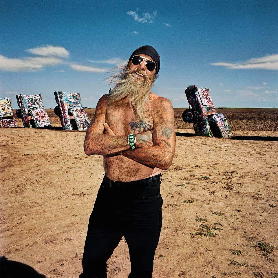 Mann mit langem Bart und Tattoos vor der Cadillac Ranch.
