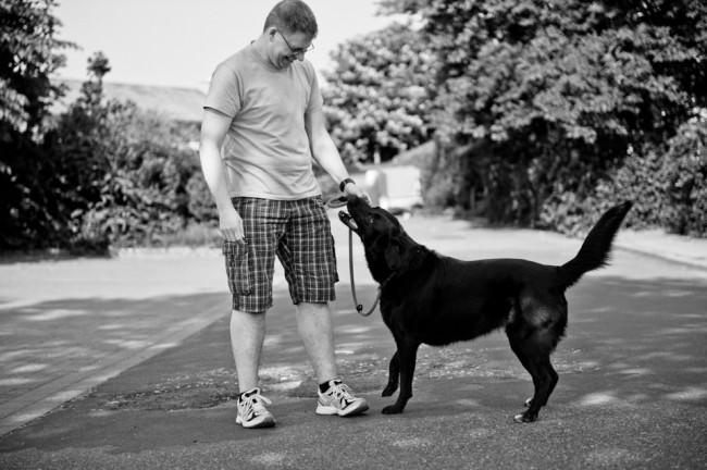 Ein Mann und ein Hund stehen auf der Straße und schauen sich an.