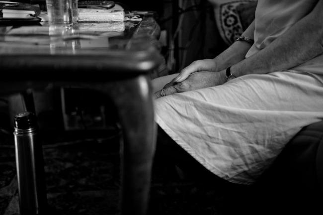 Eine Frau hat ihre Hände zusammengefaltet auf ihrem Schoß liegen.