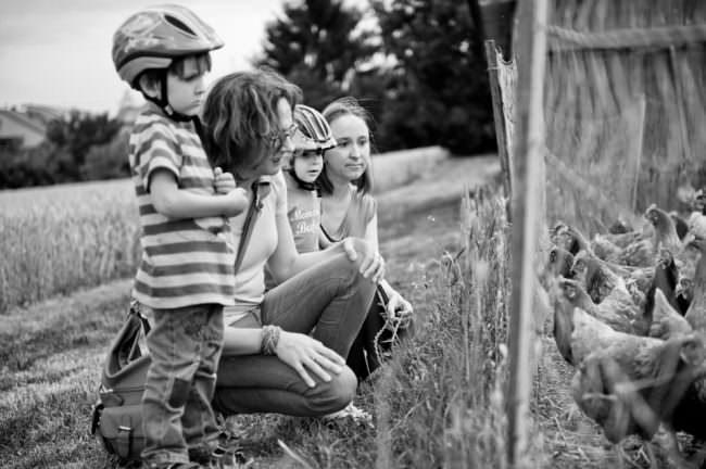 Eine Mutter hockt mit ihren Kindern vor einem Gehege.