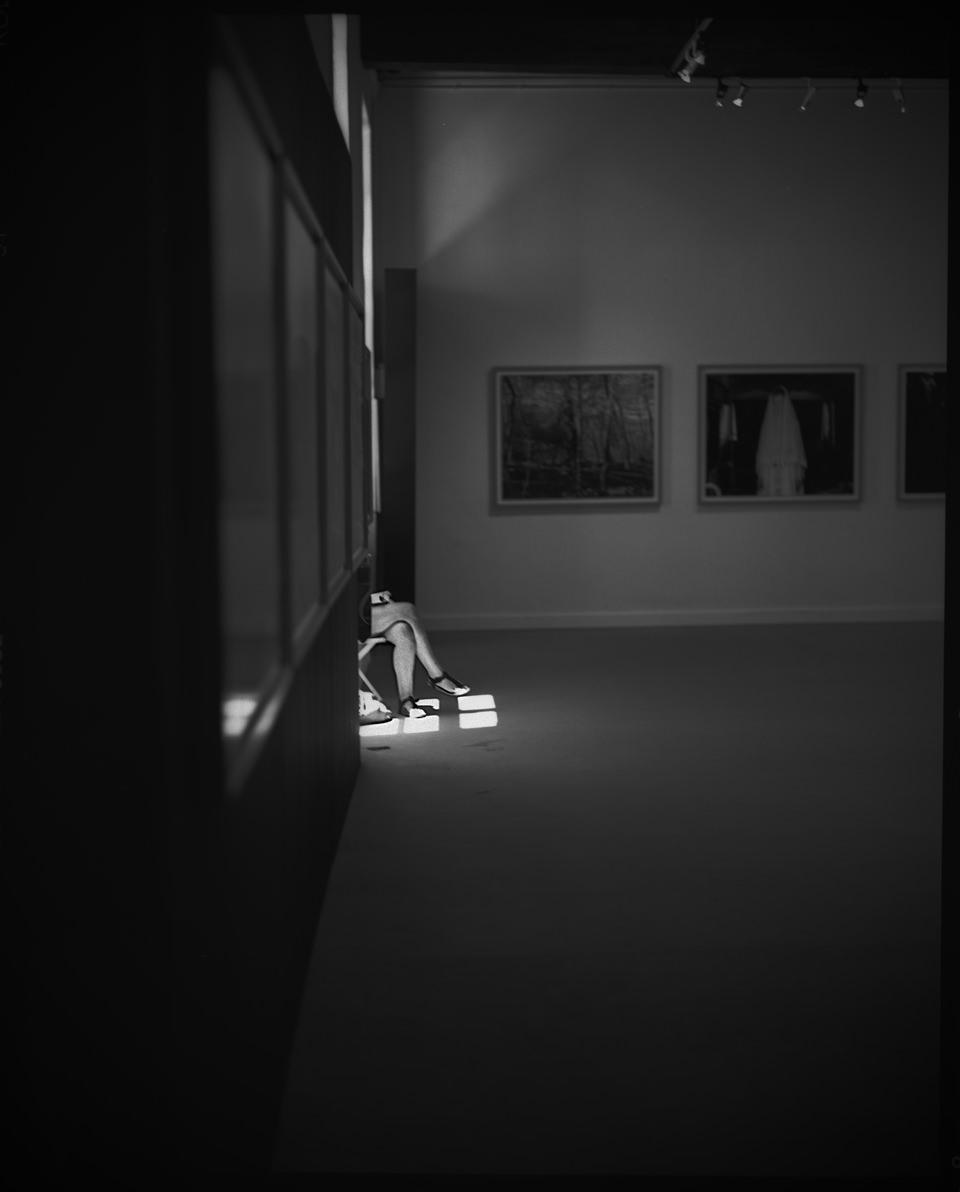 Ein Ausstellungsraum. Jemand sitzt am Fenster. Nur ein Teil ist im Lichtschein zu sehen.
