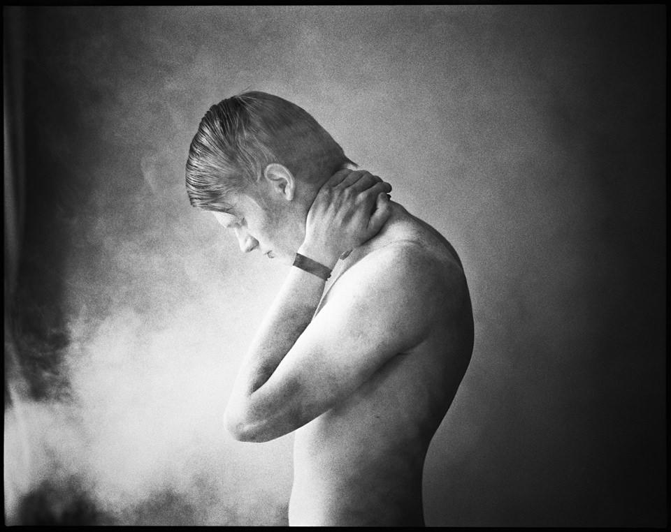 Ein Mann steht im Licht mit nackten Oberkörper.