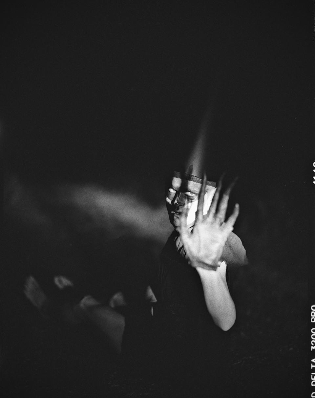 Jemand steht im Dunklen und hebt die Hand zur Kamera.