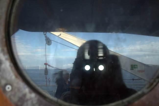 Spiegelung zweier Menschen auf einem Schiff.