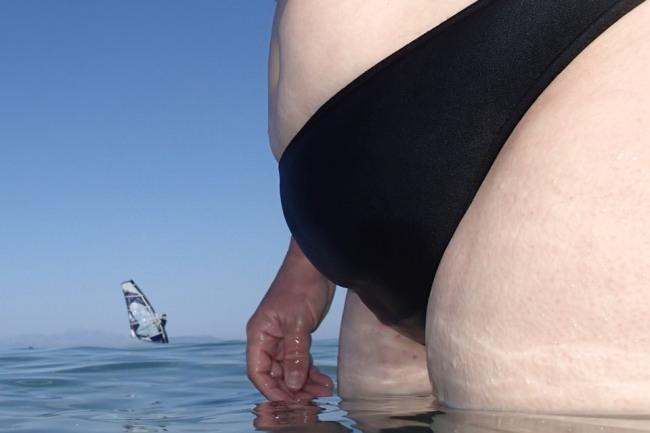 Dicker Bauch in einer Badehose im Wasser, im Hintergrund ein Surfer.