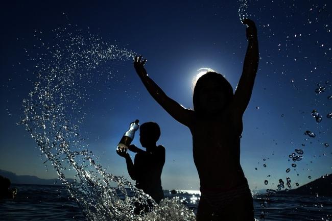 Zwei Kinder spielen im Gegenlicht im Wasser vor blauem Himmel.