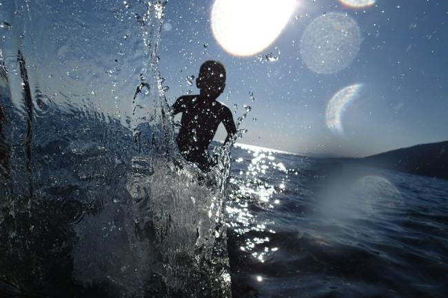 Ein Junge spielt im Wasser vor blauem Himmel.