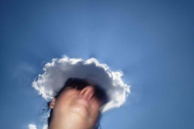 Gesicht von unten vor blauem Himmel mit Wolke.