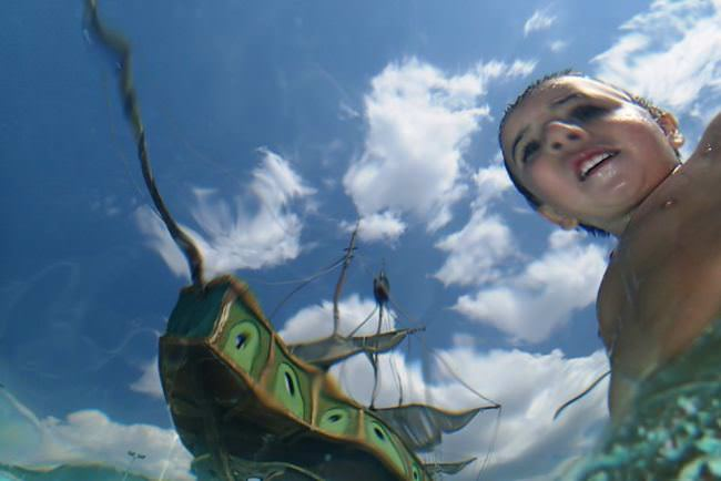 Ein Kind und ein Schiffsrumpf durch Wasser betrachtet.