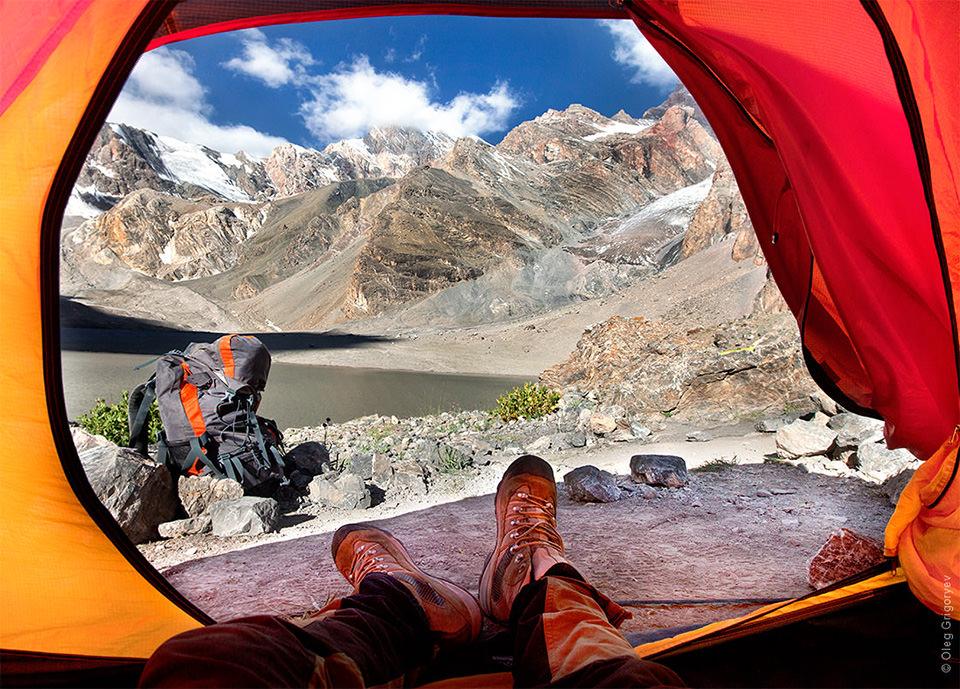 Blick aus einem Zelt heraus auf Berge.