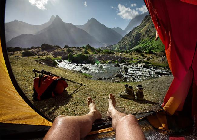 Blick aus einem zelt heraus auf eine wunderschöne Landschaft mit See und Bergen.