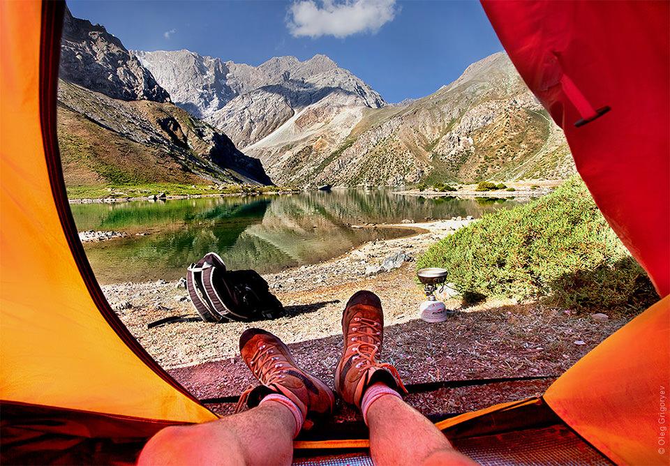 Blick aus einem zelt heraus auf einen See und Berge.