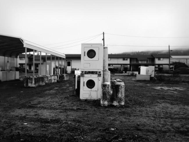 Ein alter Platz, auf dem zwei aufeinandergestapelte Waschmaschinen stehen.
