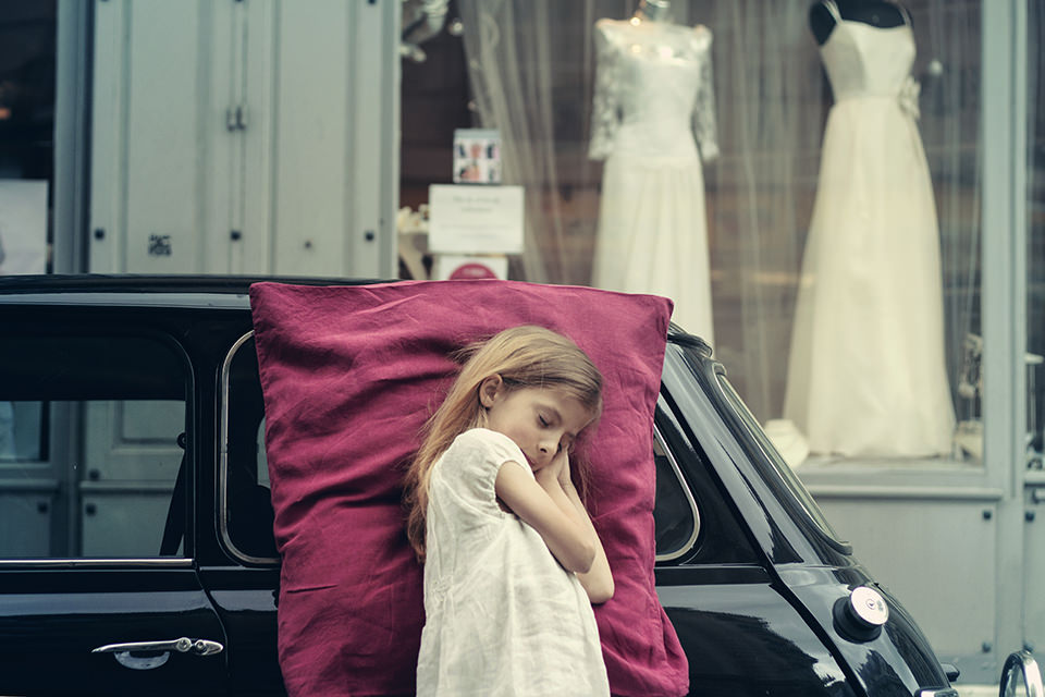 Ein schlafendes Mädchen lehnt an einem Auto vor einem Brautmodengeschäft