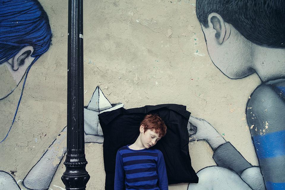 Ein rothaariger schlafender Junge lehnt an einer bemalten Wand