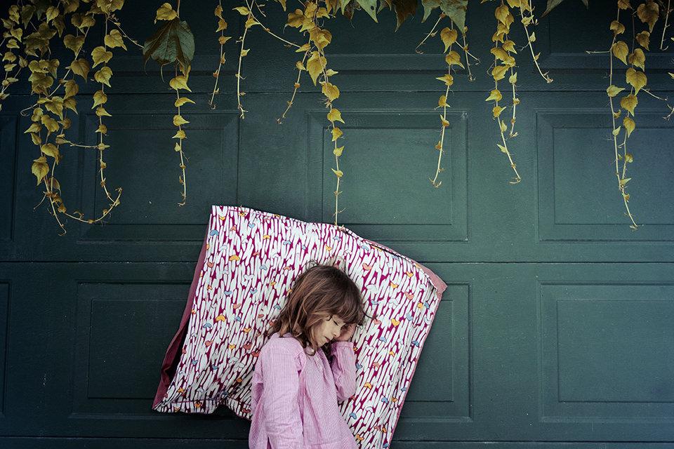 Ein schlafendes Mädchen in rosa lehnt an einer Wand