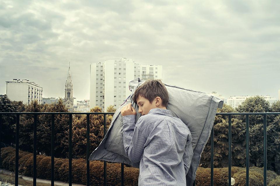 Ein schlafender Junge lehnt vor einer Großstadtkulisse