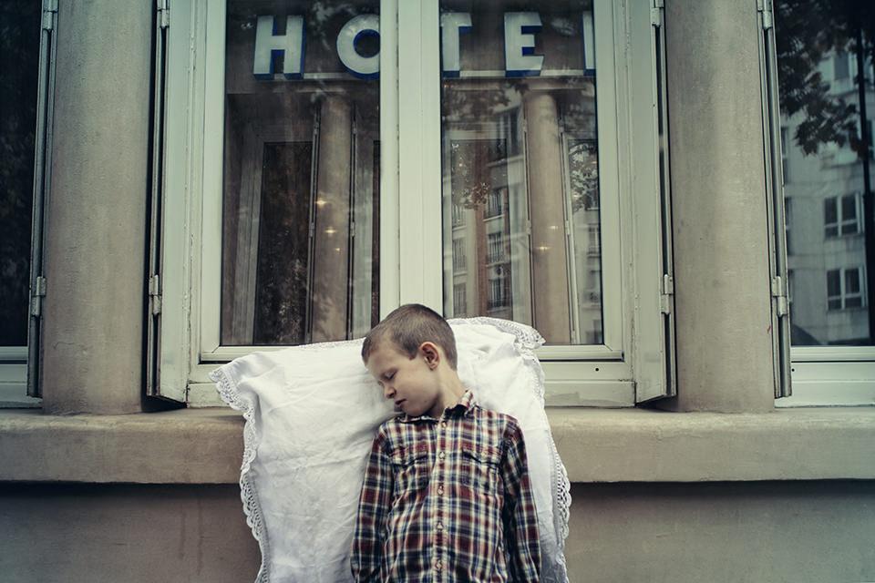 Ein schlafender Junge lehnt vor einem Hotelfenster