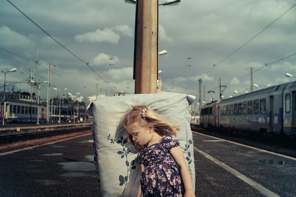 Ein schlafendes Mädchen lehnt an einem Bahnsteig