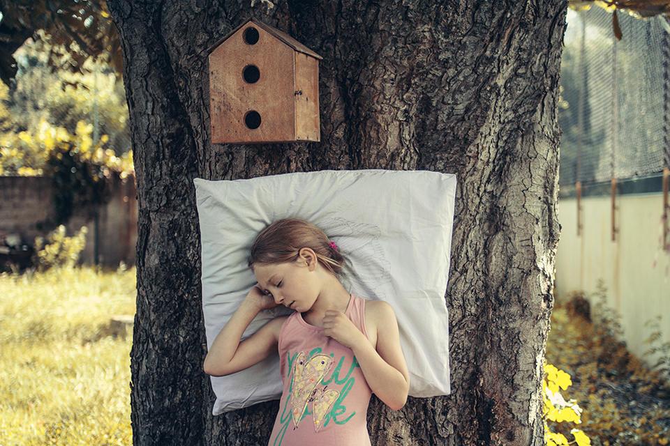 Ein schlafendes Mädchen lehnt an einem Baum, über ihr ist ein Vogelkasten.