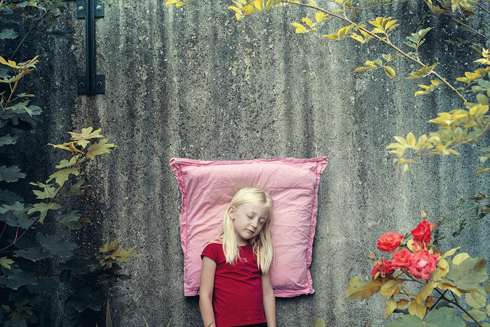 Ein auf einem rosa Kissen schlafendes Mädchen lehnt an einer Wand.