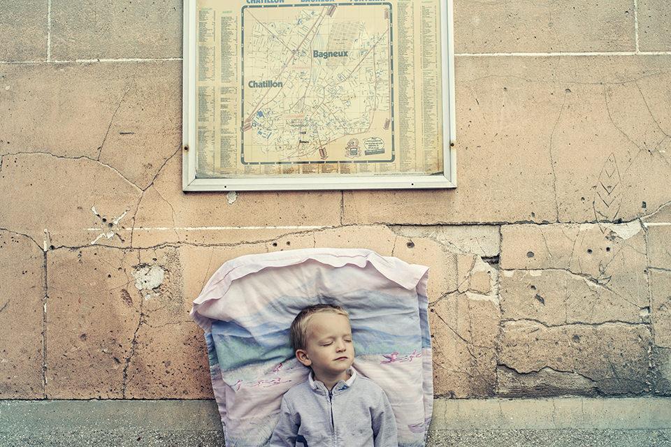Ein schlafender Junge lehnt an einer Mauer.