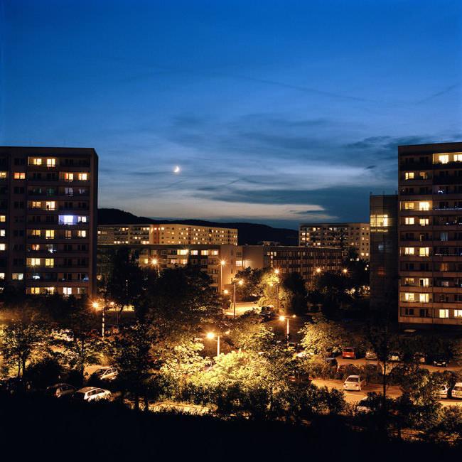 Blick auf eine Plattenbausiedlung am Abend, am Himmel die Mondsichel